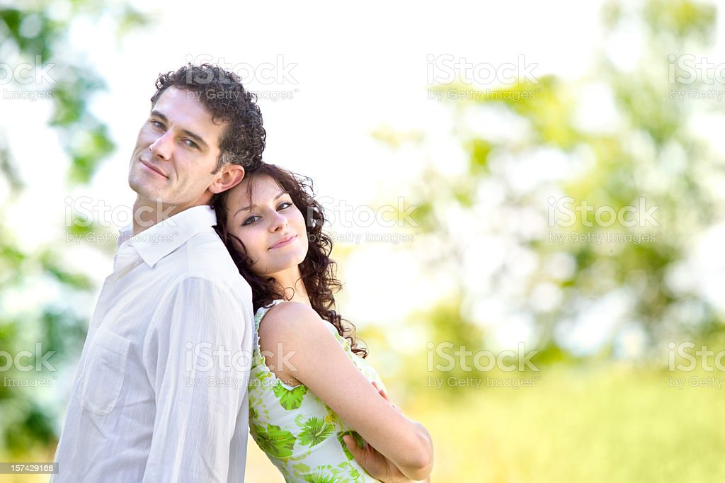 Young couple standing back to back outdoors royalty-free stock photo