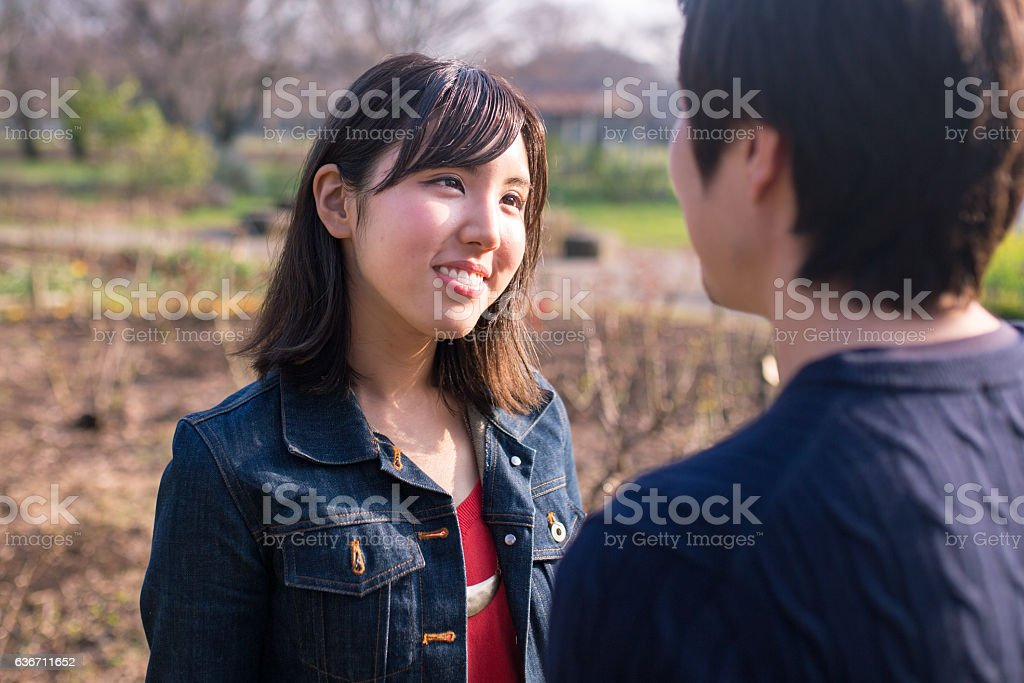 Young couple standing face to face closely stock photo