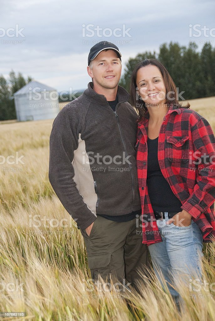 Young couple standing in a wheat field on farm stock photo