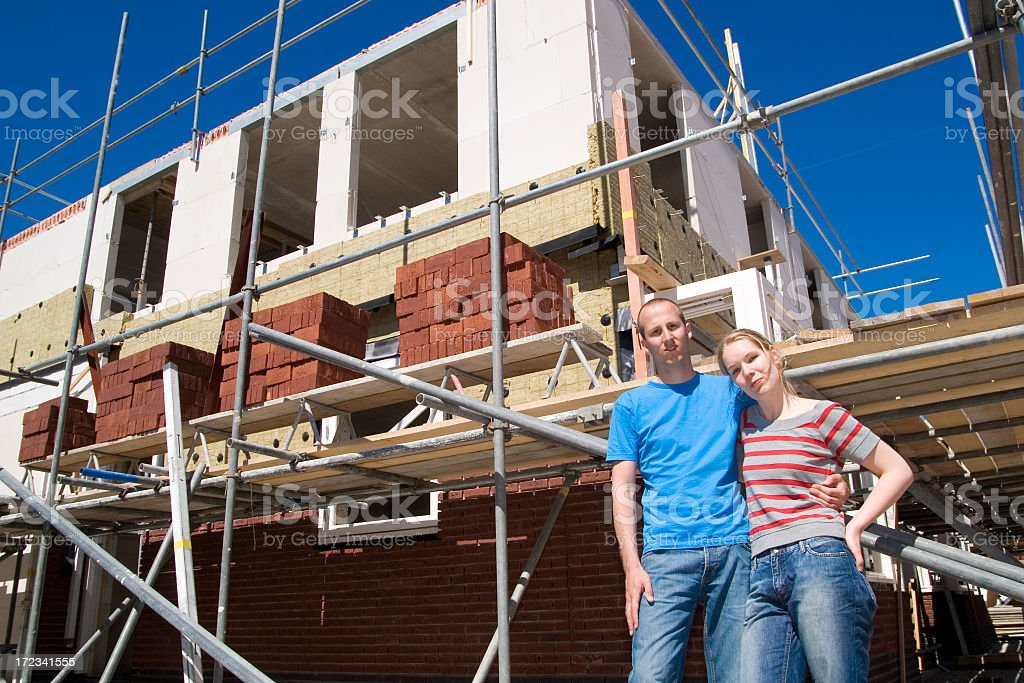 A young couple standing in front of a house construction royalty-free stock photo