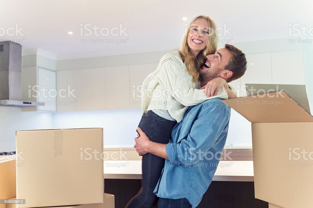 Young couple standing in new house with packing boxes. stock photo
