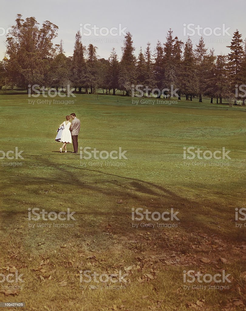 Young couple standing in park with trees in background stock photo