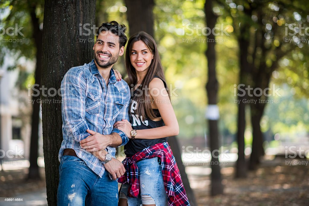 Young couple standing next to a tree in the park stock photo