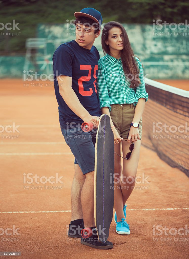 Young couple standing on a skateboard on the tennis court stock photo