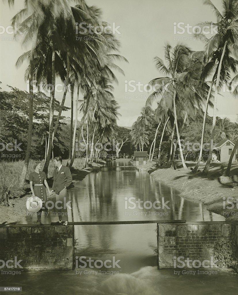 Young couple standing on footbridge, the Caribbean, Kingston, Jamaica, (B&W) stock photo