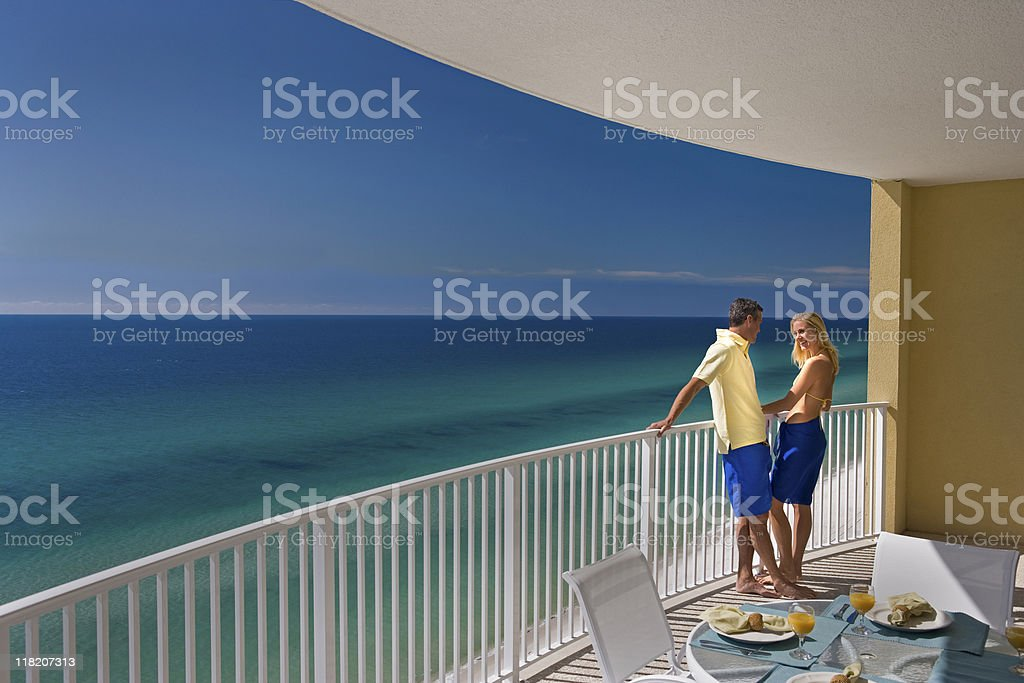 Young Couple Standing On Hotel Balcony Overlooking Ocean stock photo