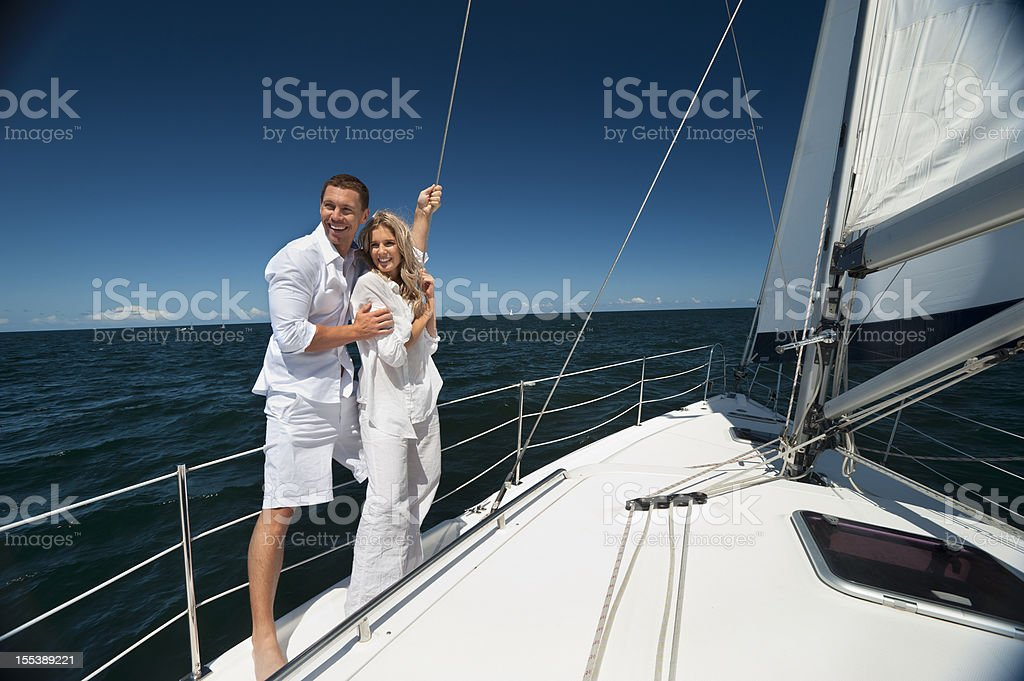 Young couple standing on sailboat cuddling each other stock photo