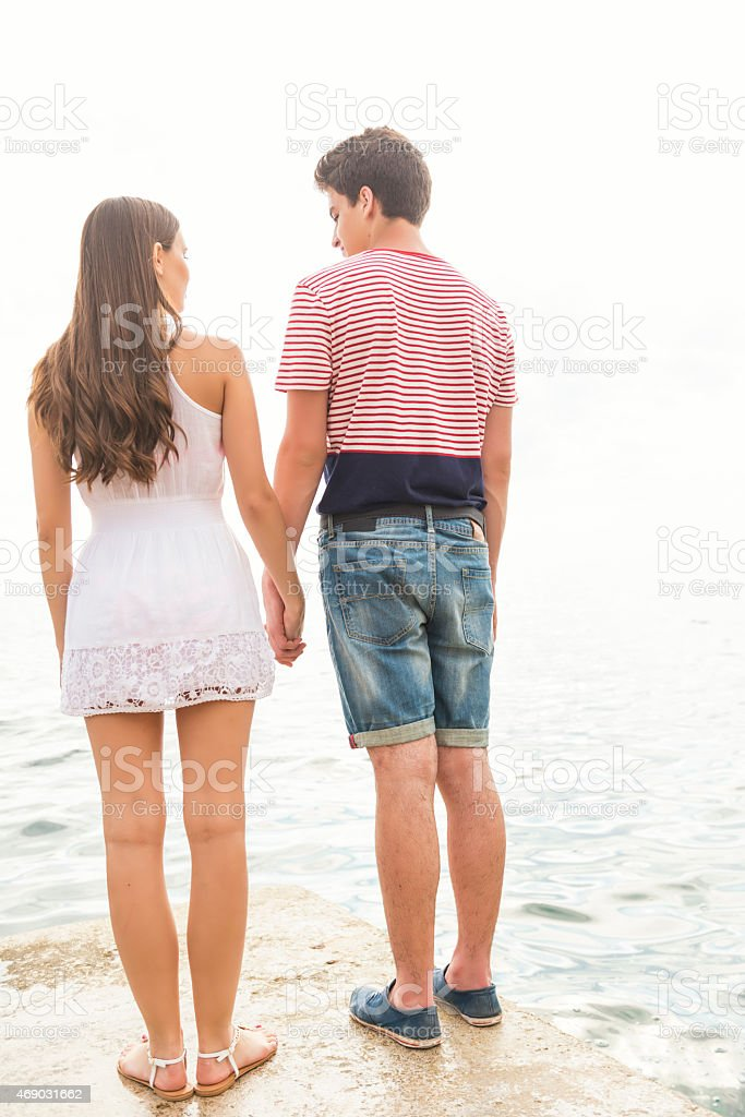 Young couple standing on the edge of pier stock photo