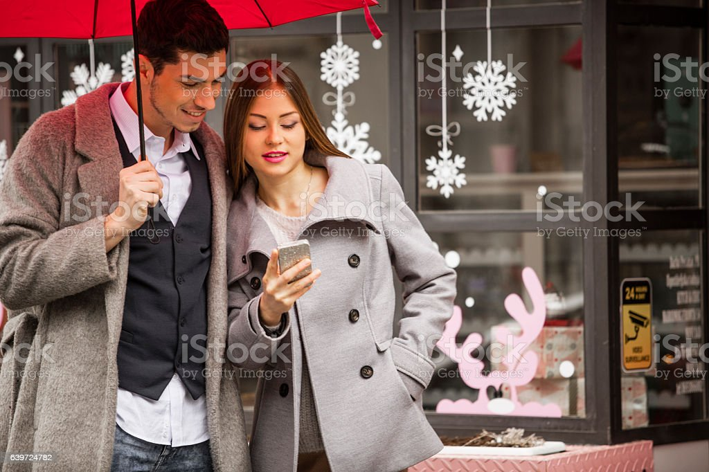 Young couple standing on the street checking their mobile device stock photo