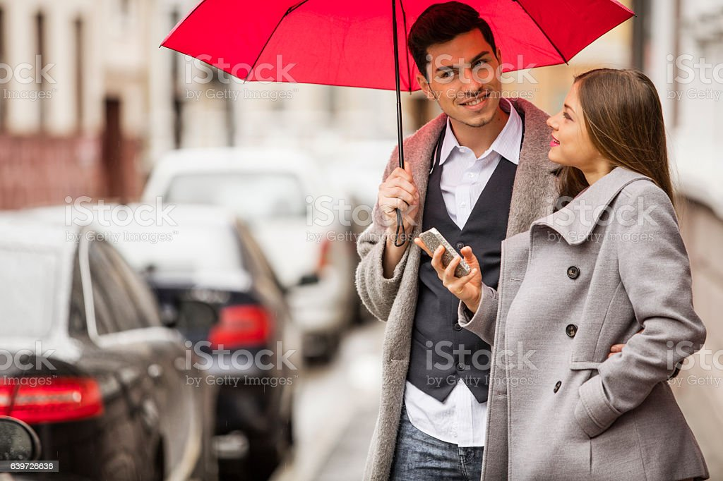 Young couple standing on the street with mobile device stock photo