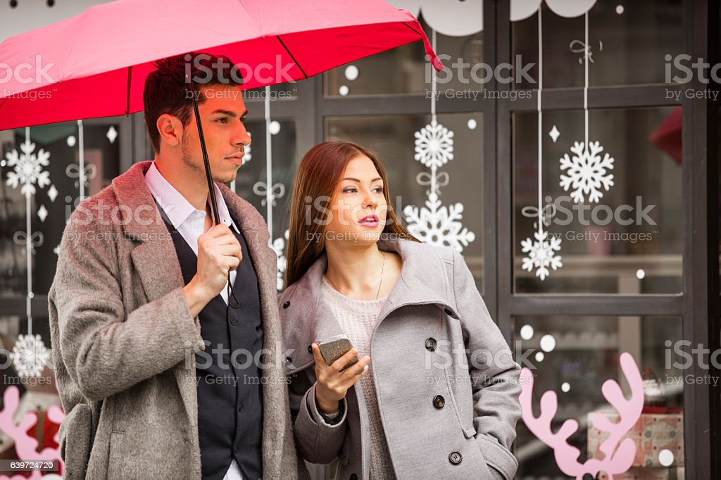 Young couple standing on the street with mobile phone stock photo
