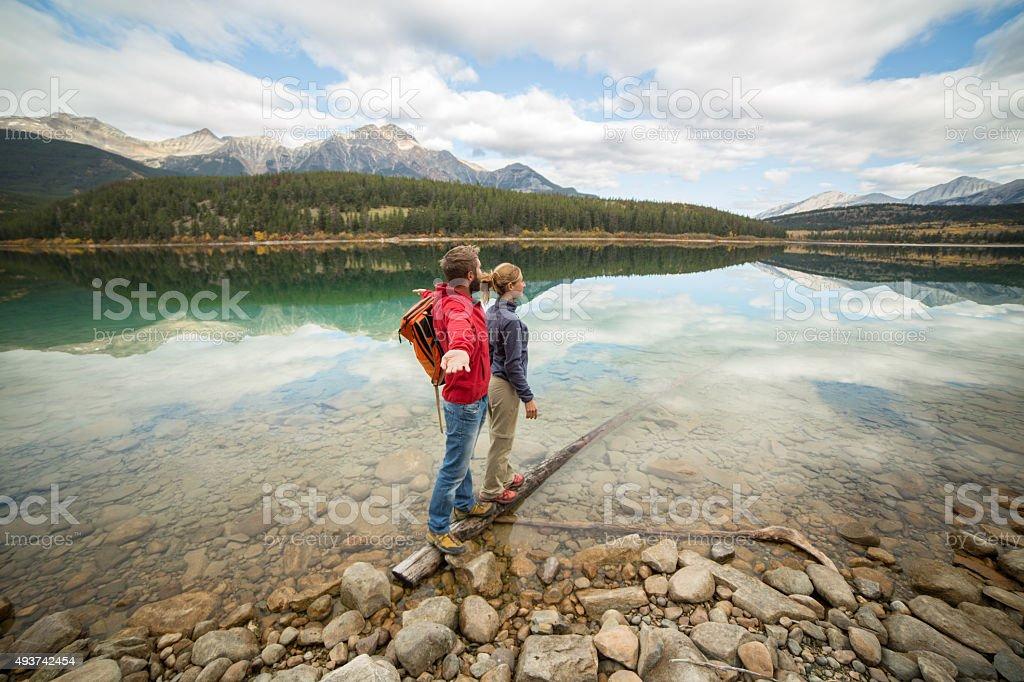 Young couple standing on tree log above lake enjoying nature stock photo