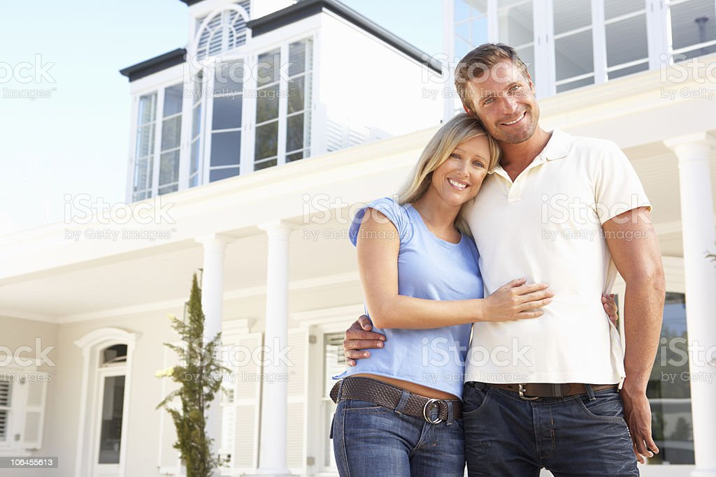 A young couple standing outside an attractive home stock photo