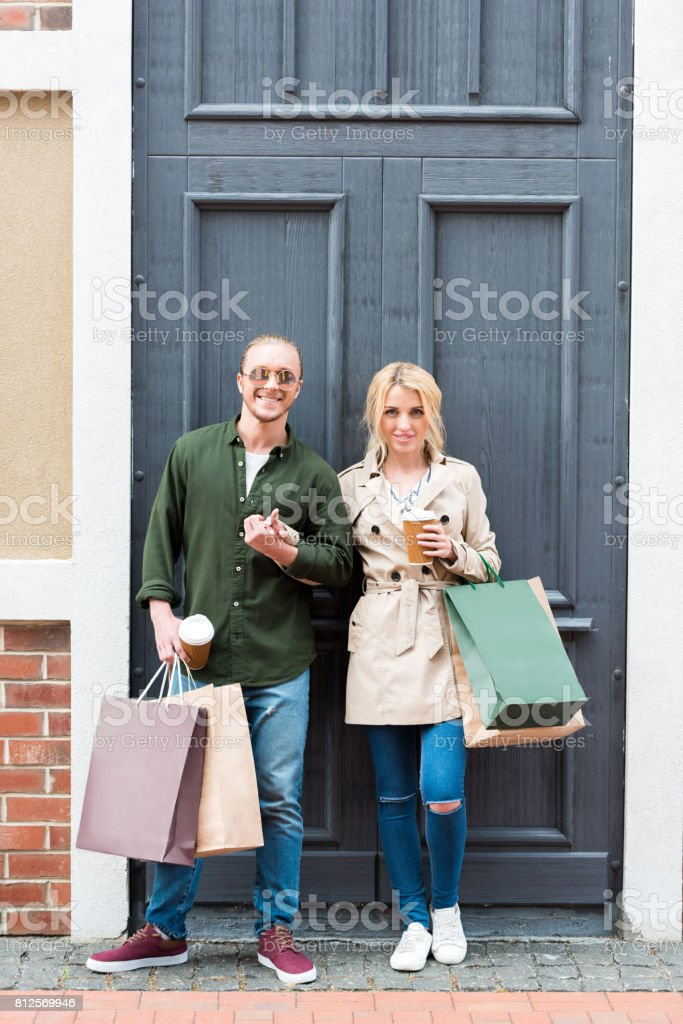 young couple standing with shopping bags and drinking coffee from disposable cups on street stock photo