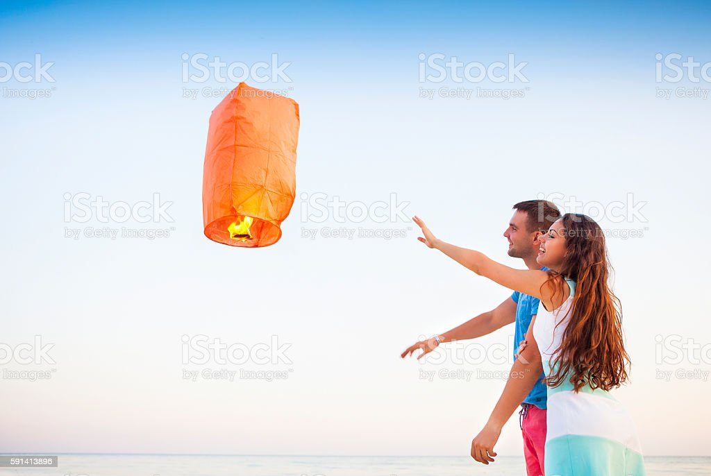 Young couple start red Chinese sky lantern in the dusk stock photo