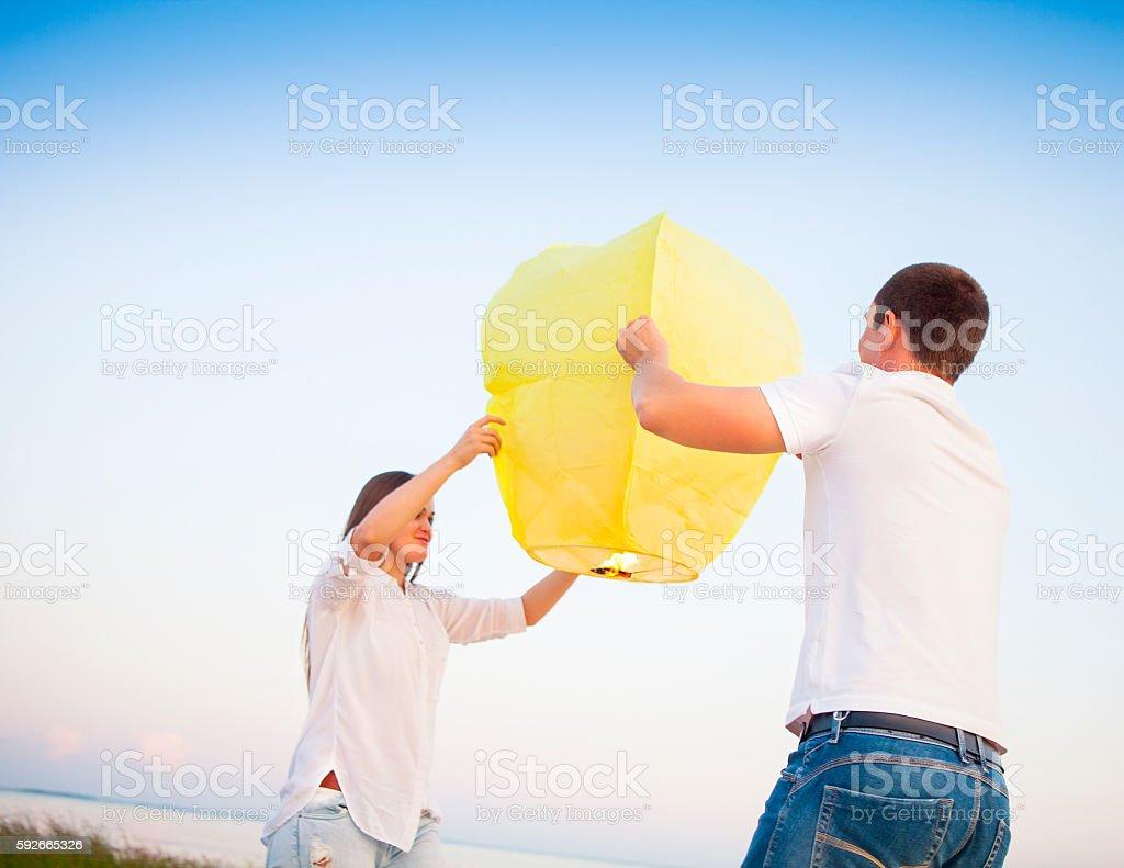 Young couple start  yellow Chinese sky lantern near the sea stock photo