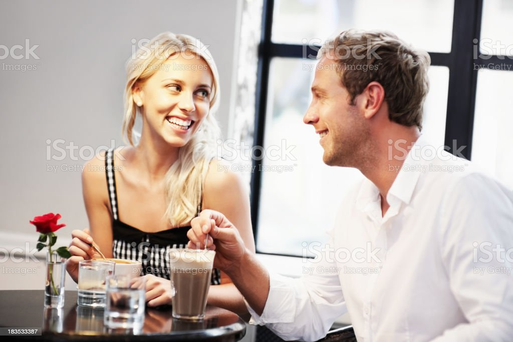 Young couple stirring coffee at cafe royalty-free stock photo