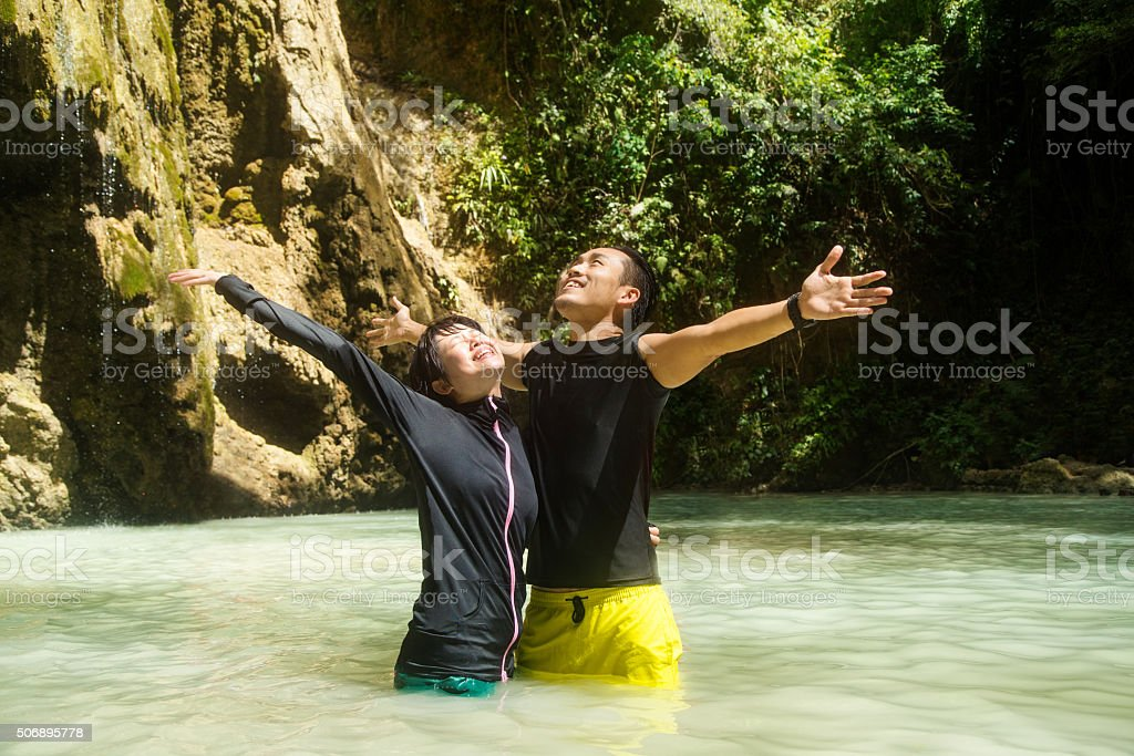 Young couple stood in a secluded waterfall stock photo