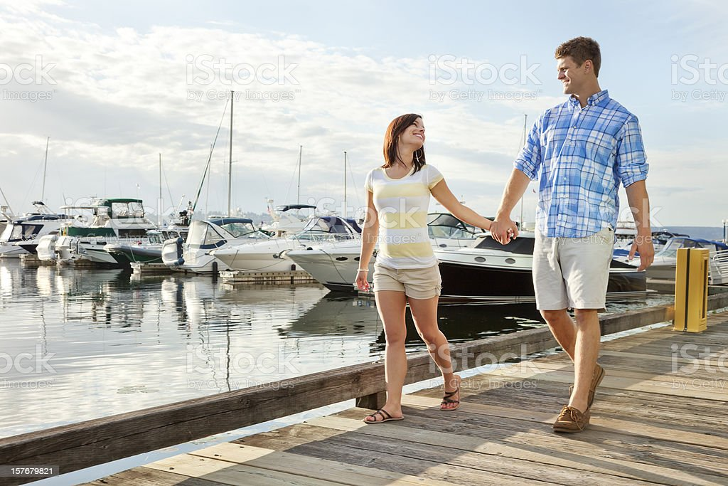 Young Couple Strolling Along Marina Boardwalk stock photo
