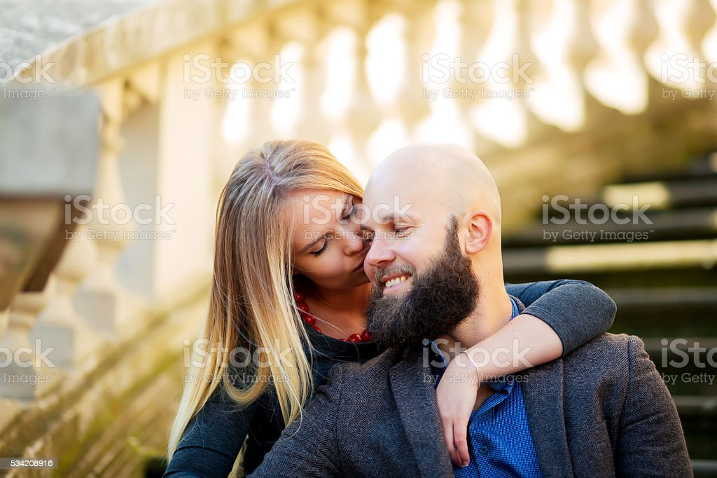 Young couple, stylishly dressed, sitting on the steps, against royalty-free stock photo