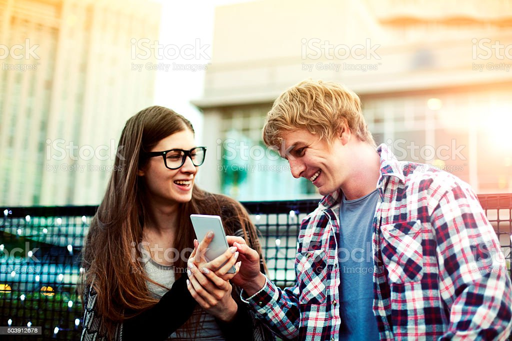 Young couple surf the internet at mobile phone outside, Tokyo stock photo
