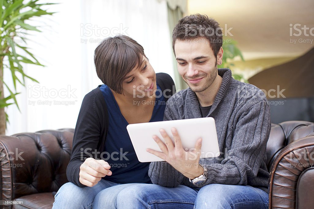 Young couple surfing the web on their tablet royalty-free stock photo