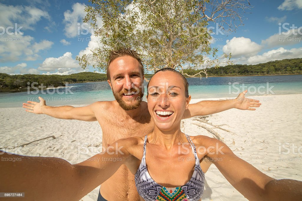 Young couple take a selfie portrait by a blue lake stock photo