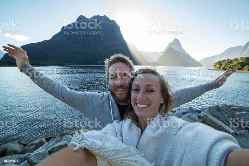 Young couple take selfie portrait in Milford sound, NZ stock photo