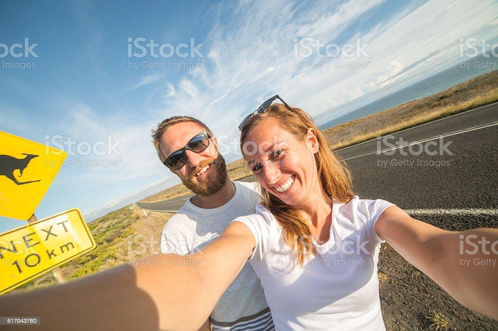 Young couple take selfie portrait near kangaroo warning sign-Australia stock photo