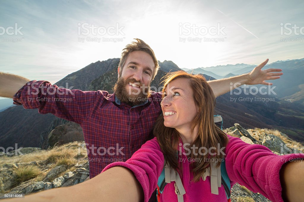 Young couple takes selfie portrait on mountain trail stock photo