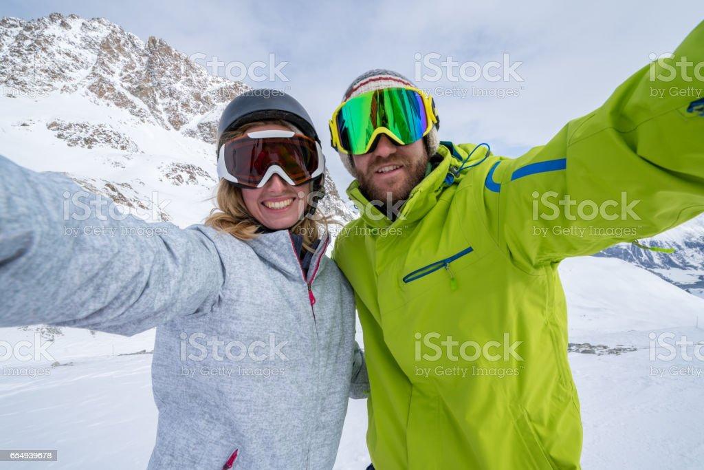Young couple takin selfie on ski slope, Switzerland stock photo