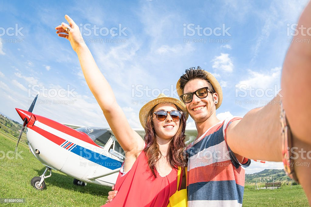 Young couple taking selfie at lightweight airplane travel stock photo