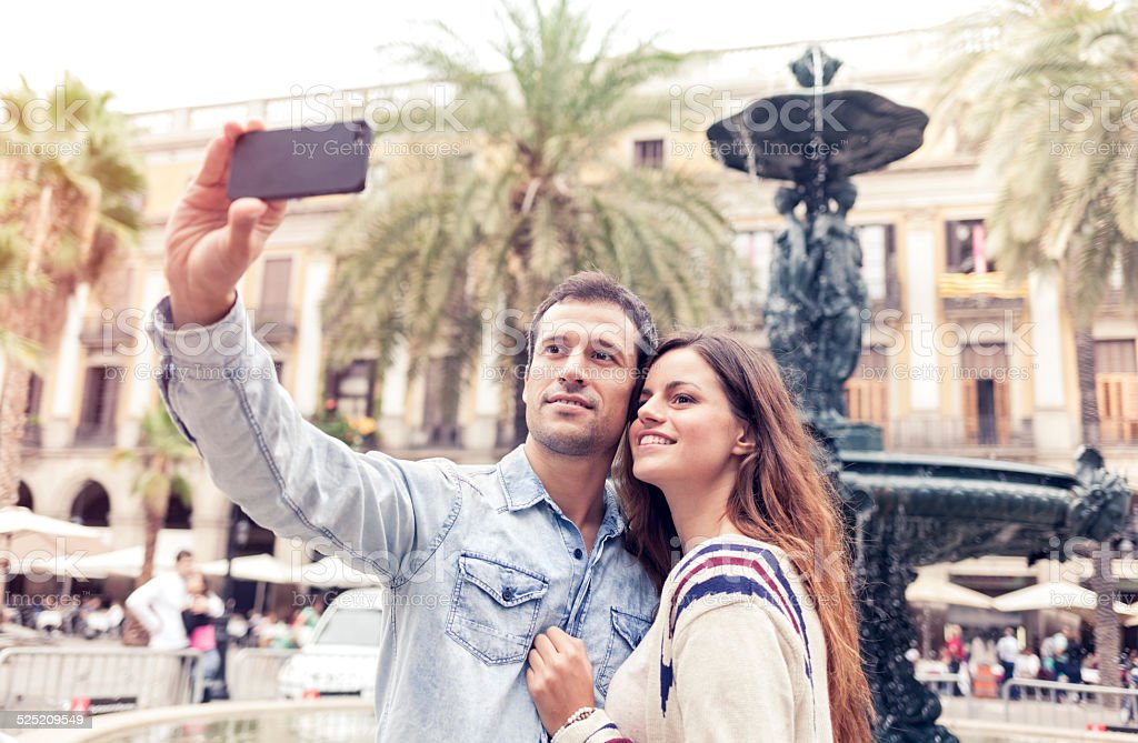 Young couple taking selfie on Plaza Real (Barcelona, Catalonia, Spain). stock photo