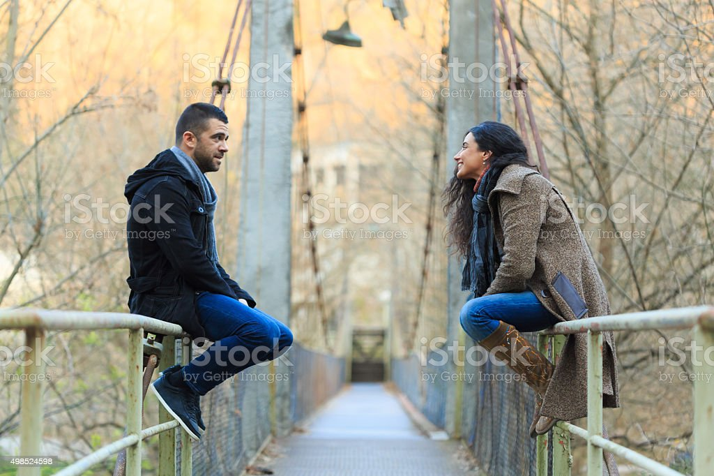 Young couple talking on bridge under autumn sun stock photo