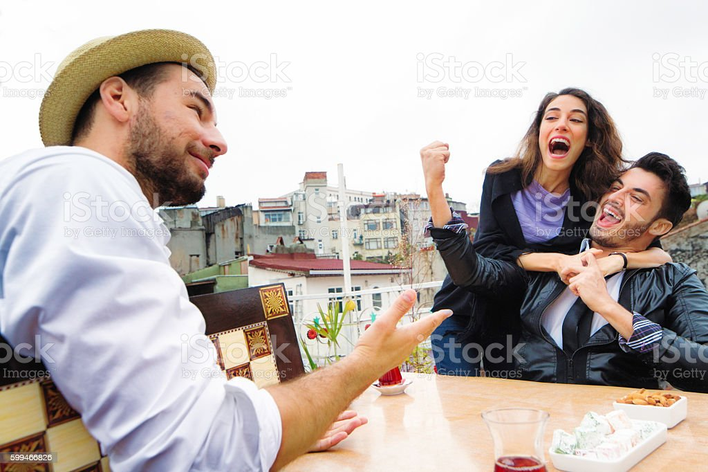 Young couple teasing friend after winning board game stock photo