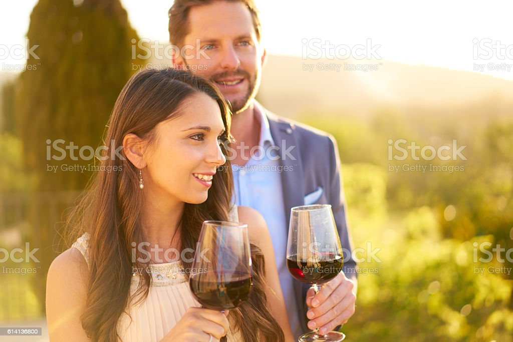 young couple testing red wine outdoors in winery stock photo