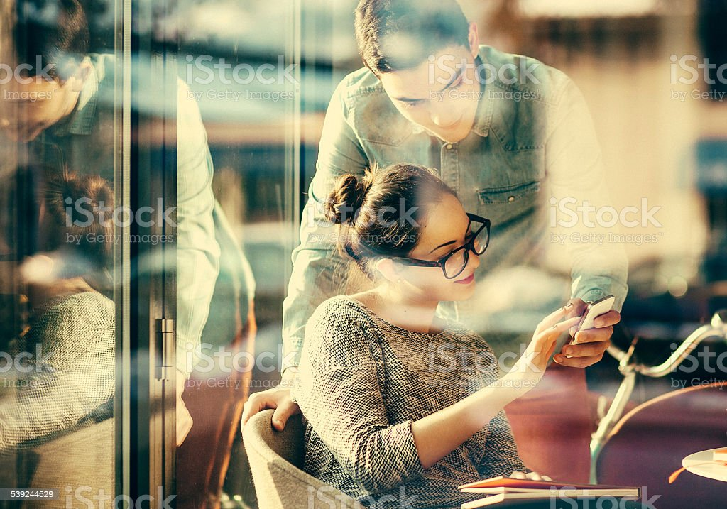 Young couple text messaging at the coffee shop stock photo