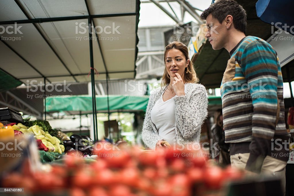 Young couple thinking which groceries to buy on farmer's market. stock photo