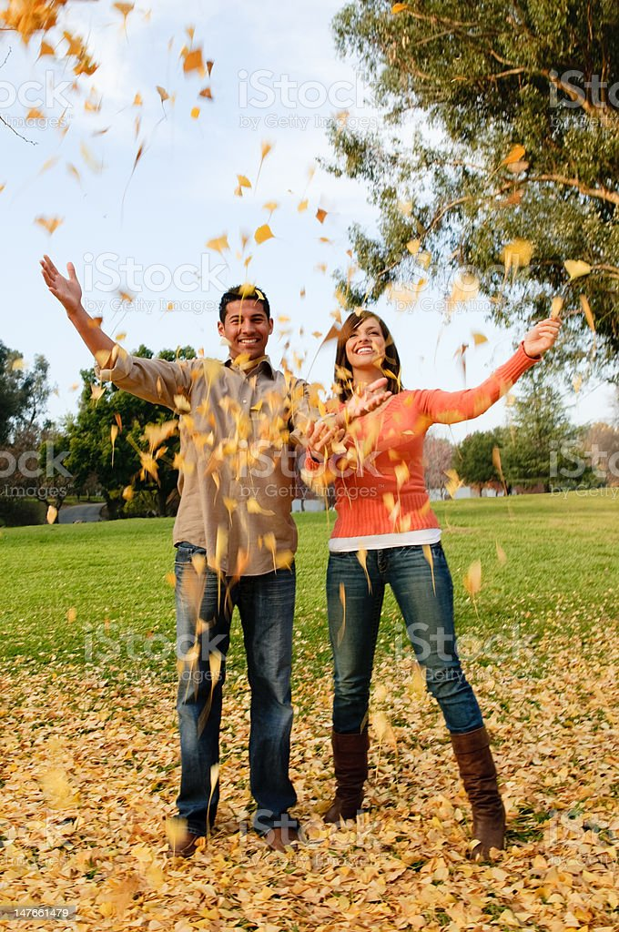Young couple throw leaves into air in park stock photo