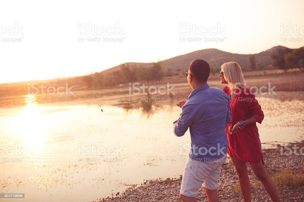 Young couple throwing pebbles into the lake stock photo