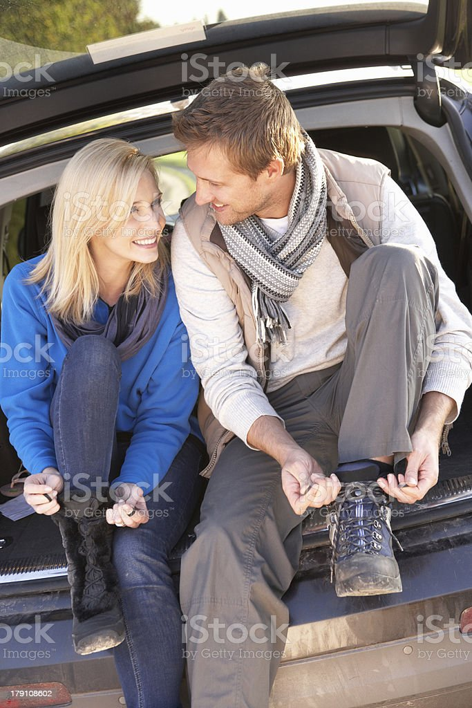 Young couple tie boots at rear of car royalty-free stock photo