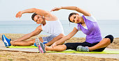 Young couple training yoga poses sitting on beach