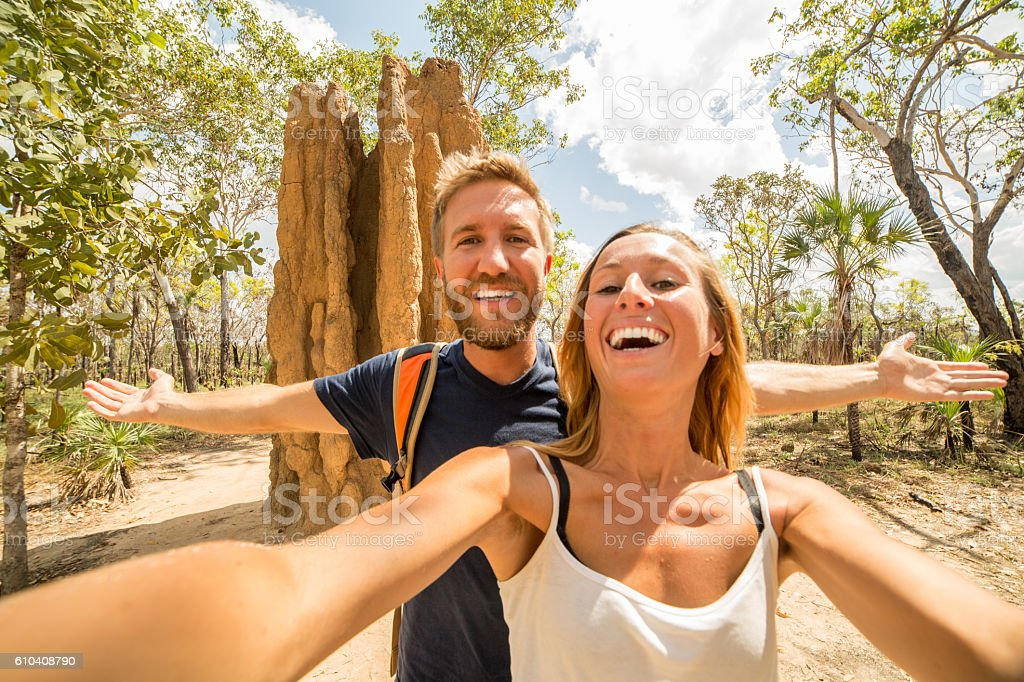 Young couple traveling take selfie portrait with huge termite mound stock photo