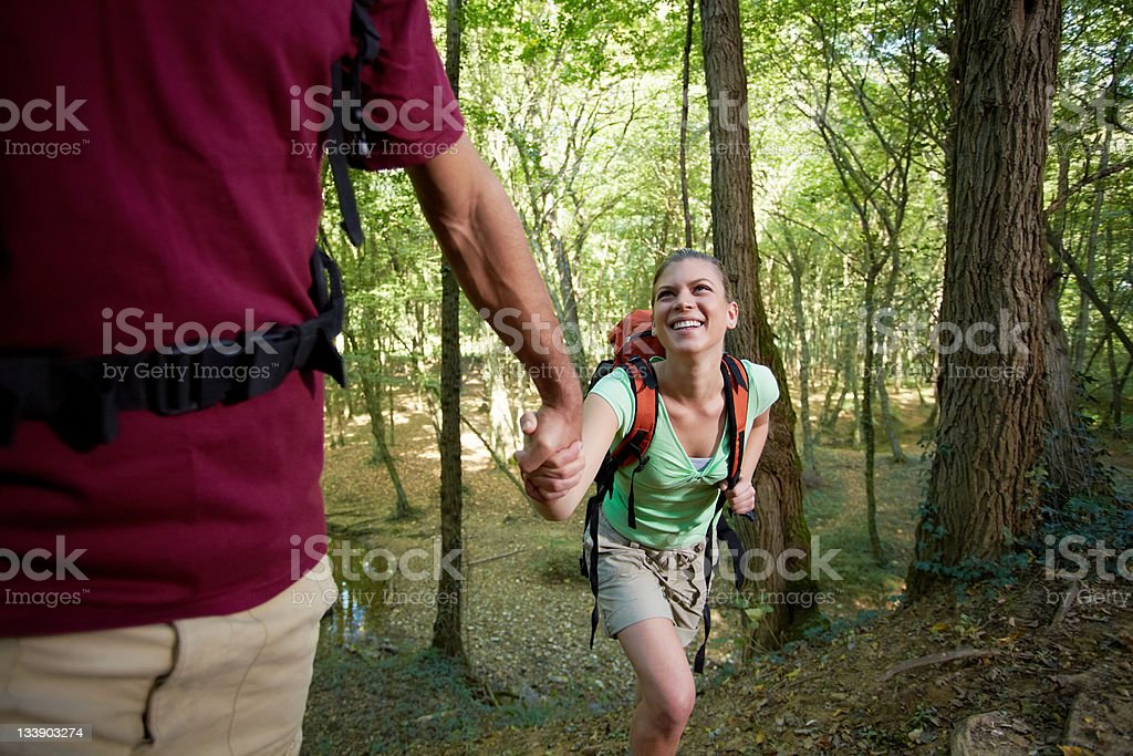 young couple trekking in forest and holding hands royalty-free stock photo