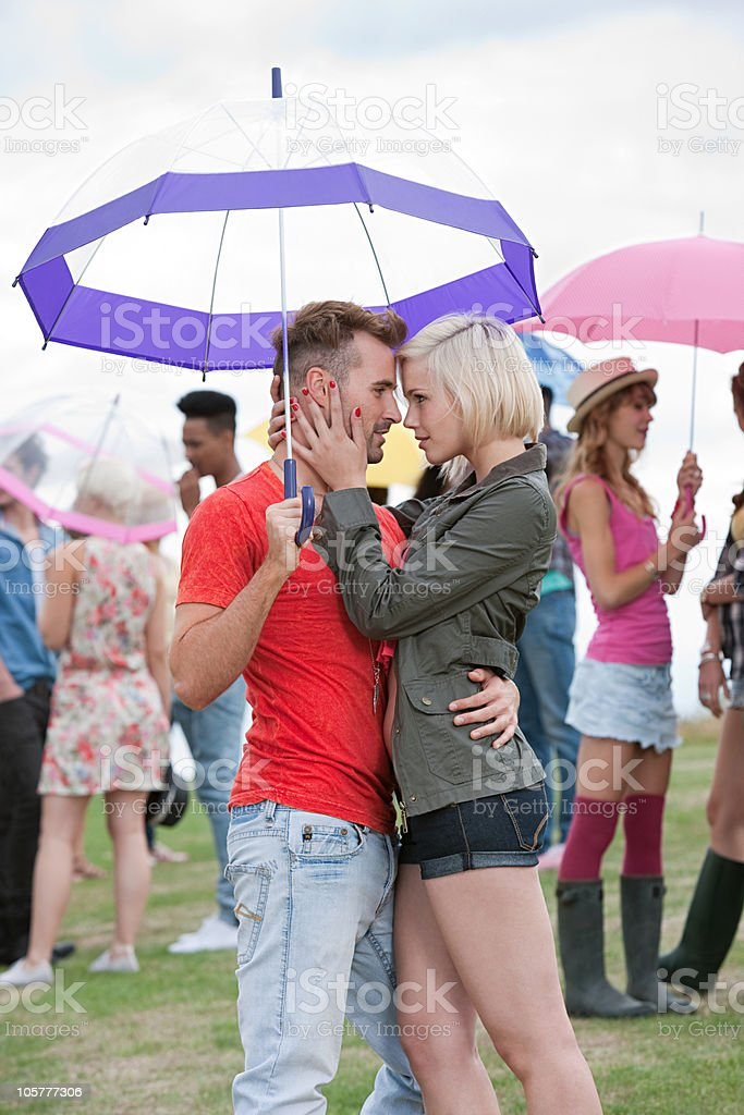 Young couple under umbrella at festival royalty-free stock photo