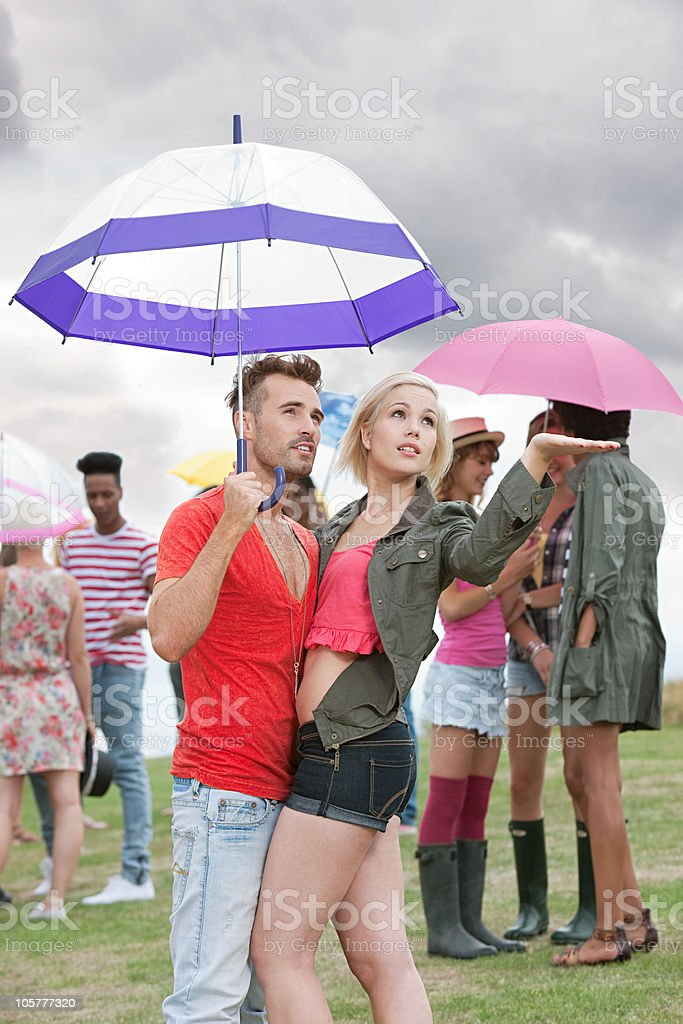 Young couple under umbrella at festival, testing for rain royalty-free stock photo