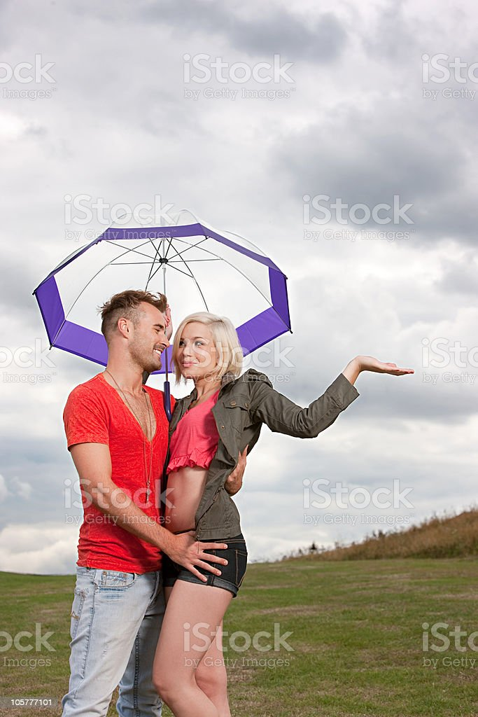 Young couple under umbrella, testing for rain royalty-free stock photo