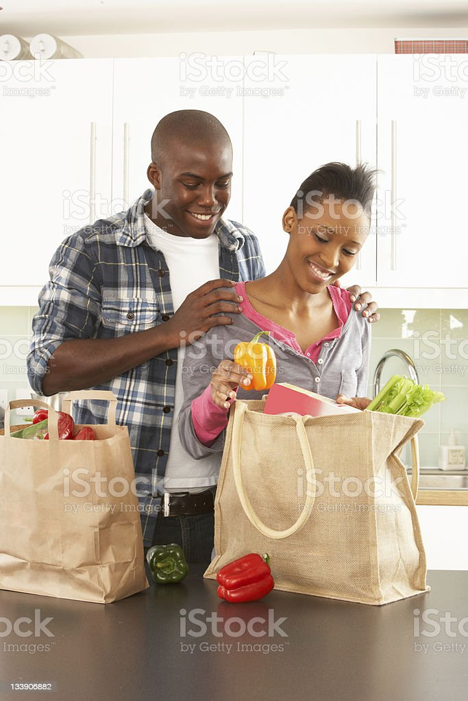 Young Couple Unpacking Shopping In Kitchen stock photo