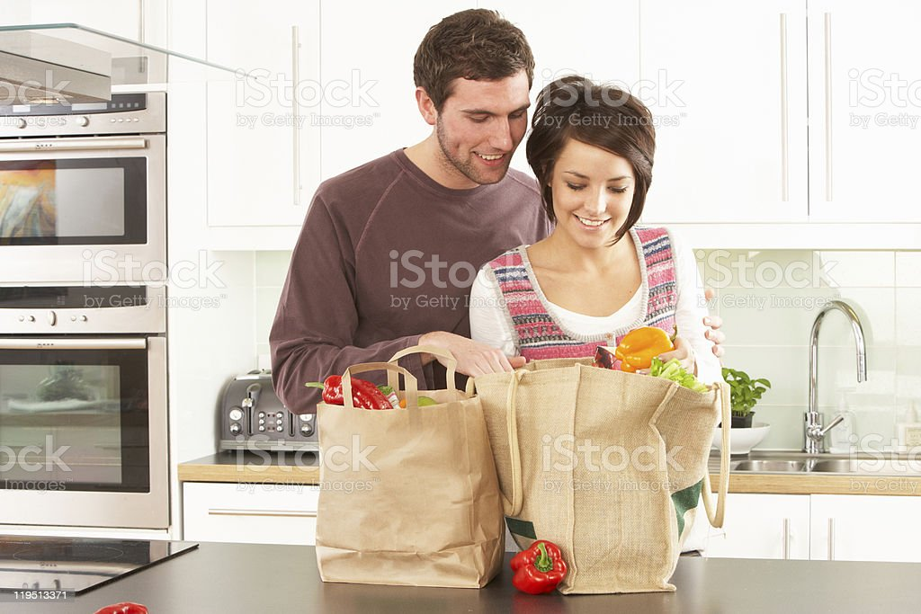 Young Couple Unpacking Shopping In Modern Kitchen stock photo