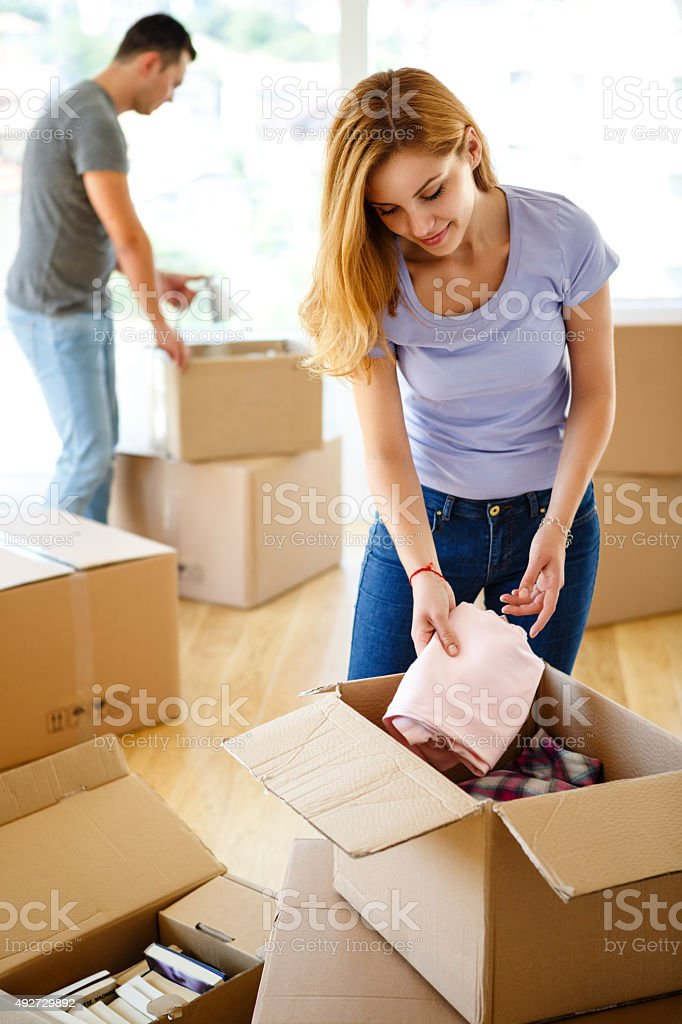 Young couple unpacking together and having fun stock photo